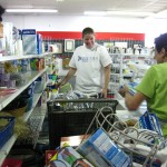 Stocking Bric-a-Brac shelves at Norristown Impact Thrift Stores