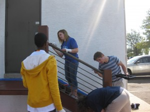 Students from Christopher Dock paint a stair rail outside of the Montgomeryville Impact Thrift Store