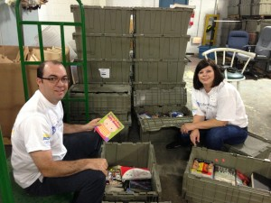 Liberty Mutual Volunteers sort books along side Impact Thrift Stores book department employees