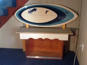 Bench created by combining a surf board headboard and kitchen cabinet